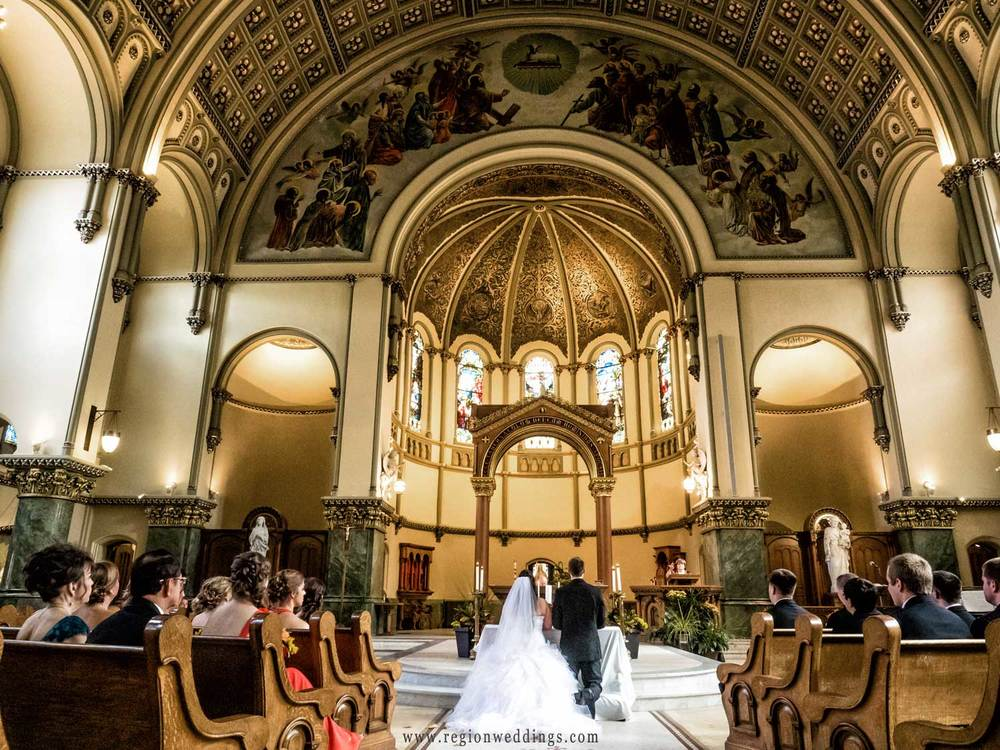 The bride and groom pray at Saint Josaphat Roman Catholic Church.
