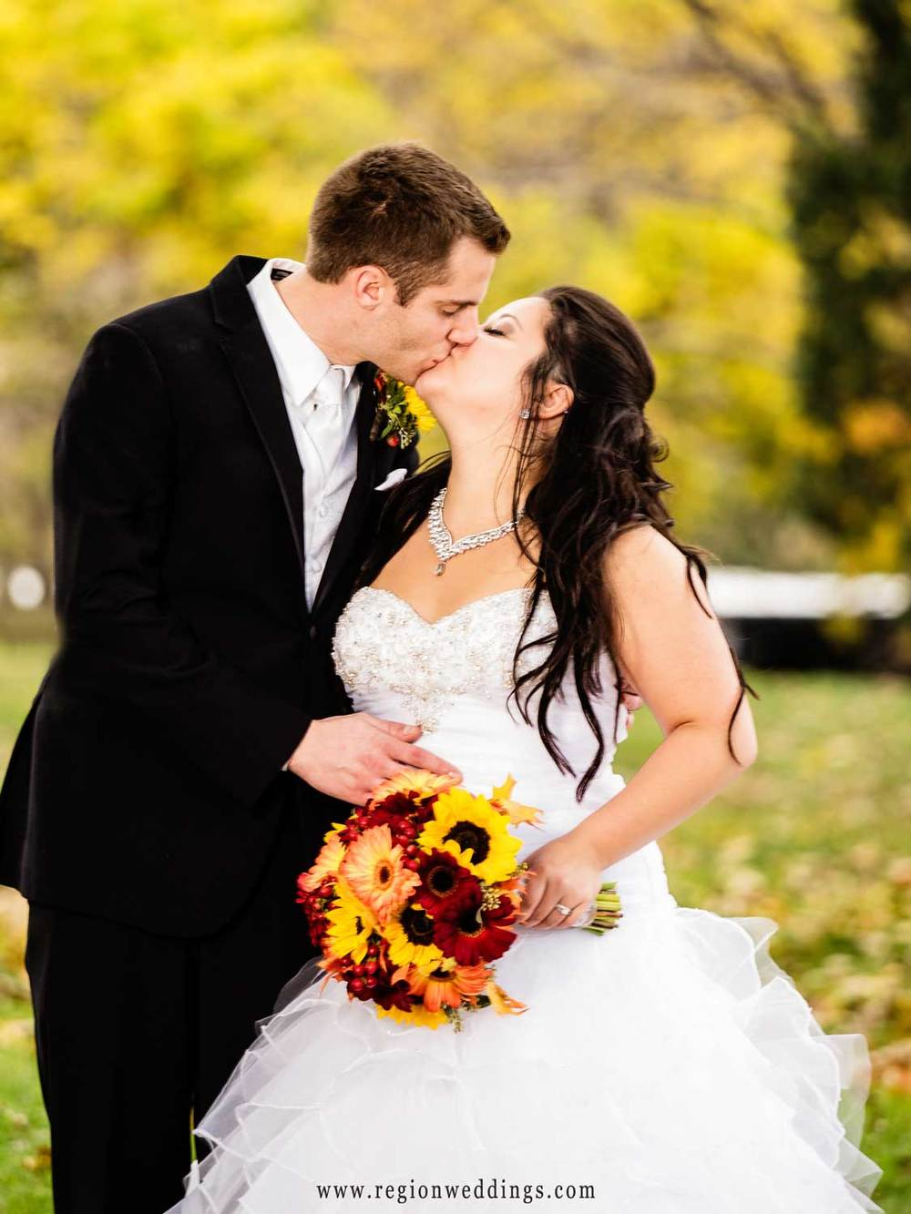 Fall colors in the background as the bride and groom kiss near Lincoln Park.