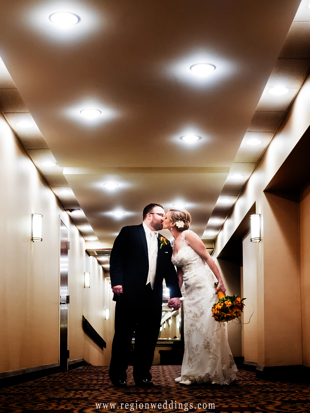 The bride and groom kiss in the hallway at Radisson Hotel.