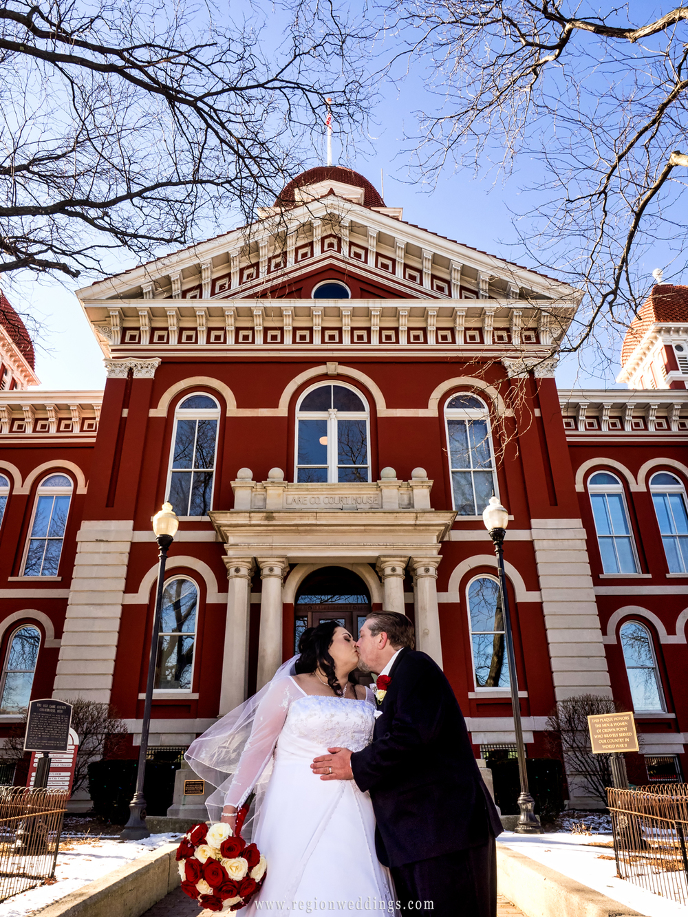 Bride and groom kiss at the Old Crown Point Courthouse on Valentine's Day weekend.