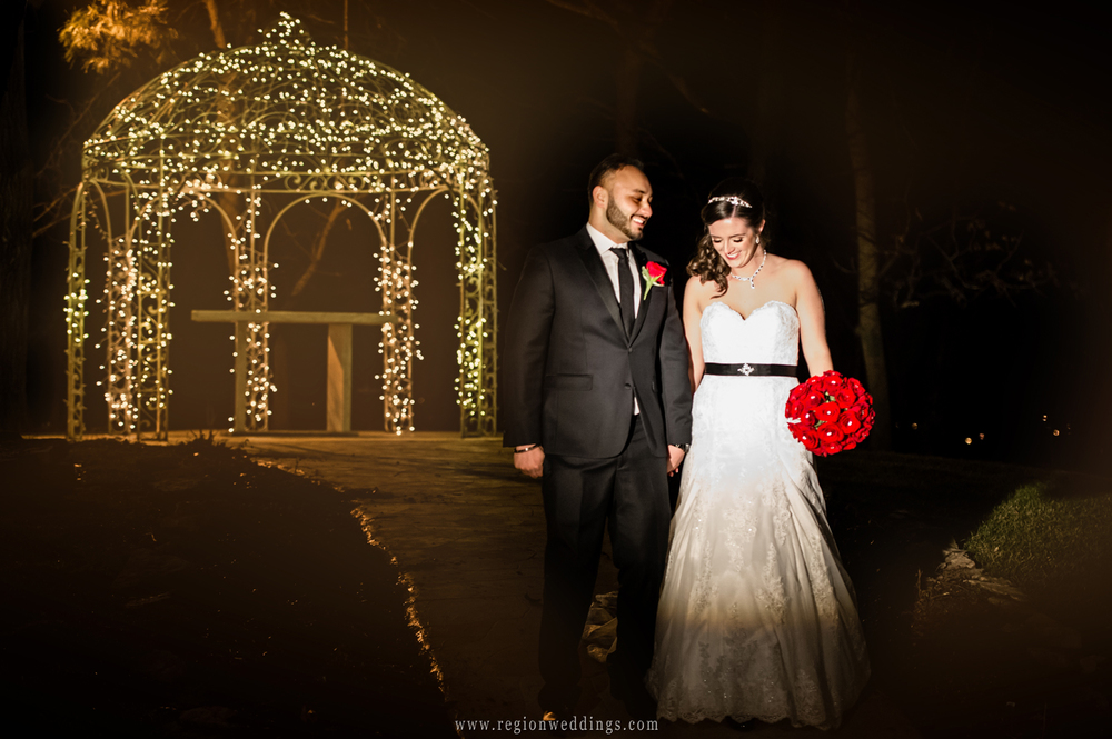 Bride and groom take a night time stroll in front of the lighted gazebo at Meyer's Castle in Dyer, Indiana.