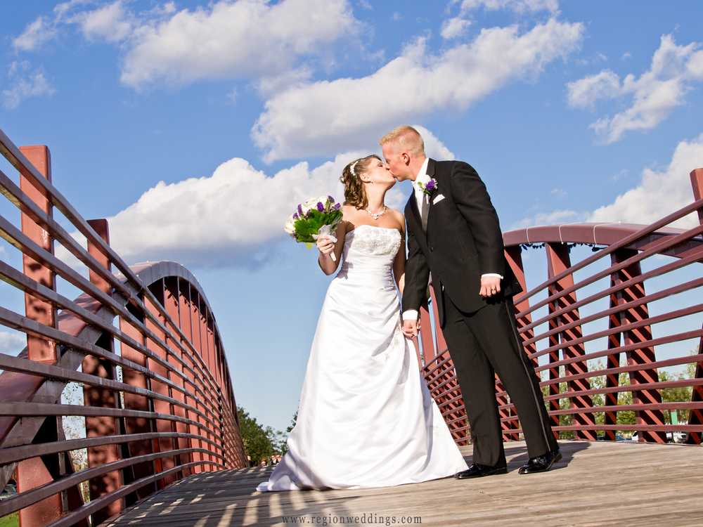 The bride and groom kiss on the bridge at Centennial Park in Munster.