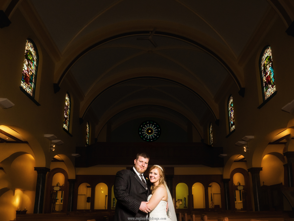 The bride and groom stand center aisle at St. Peter's Catholic Church in Laporte, Indiana.