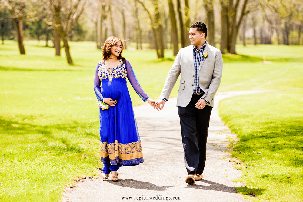 A couple takes a walk at Briar Ridge Country Club for a maternity photo session.