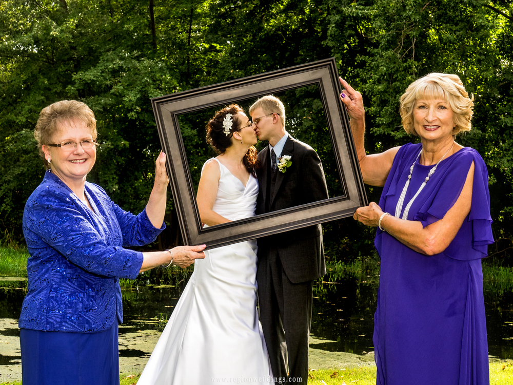 Moms of the bride and groom hold a picture frame in front of their kids on wedding day.