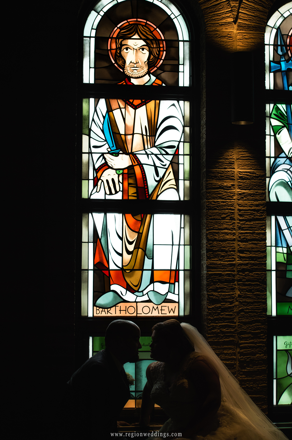 A silhouette of the bride and groom in front of stained glass windows at Saint Maria Goretti Church in Dyer, Indiana.
