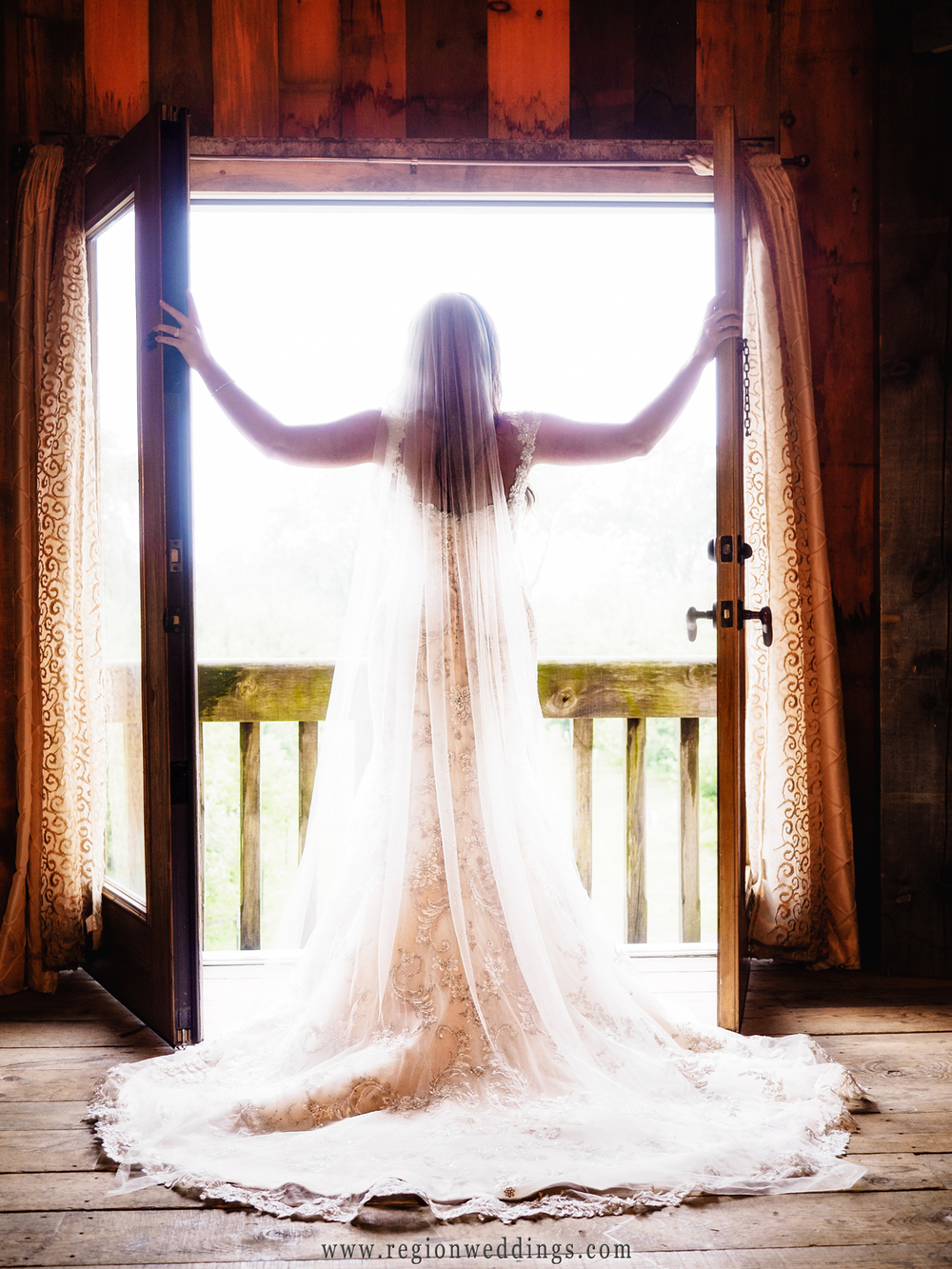 The bride opens the balcony doors in the bridal suite at County Line Orchard.