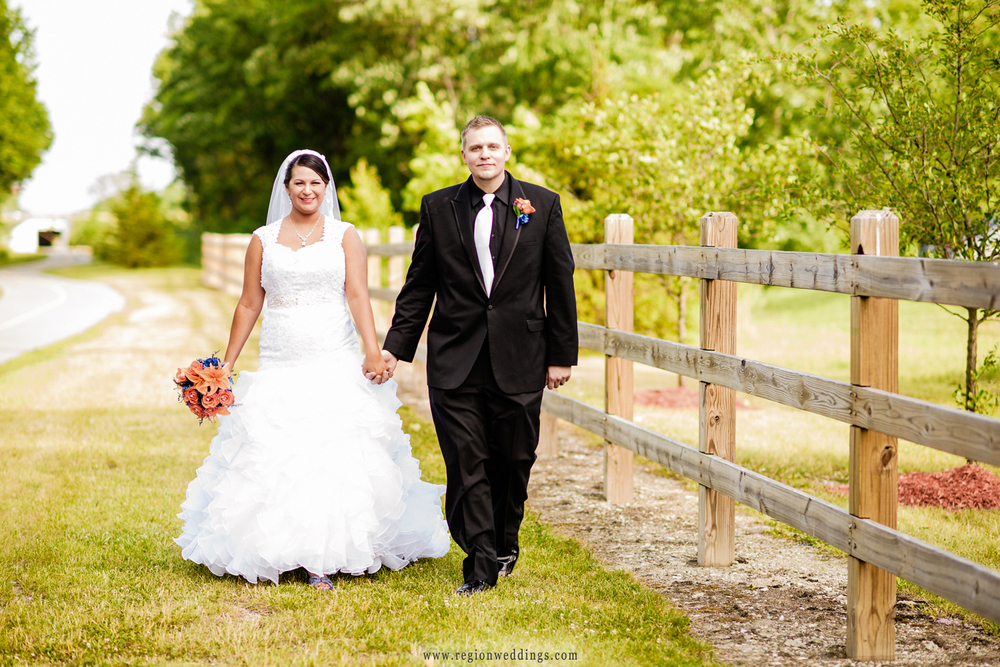 Bride and groom take a romantic walk along a rustic, wooden fence.