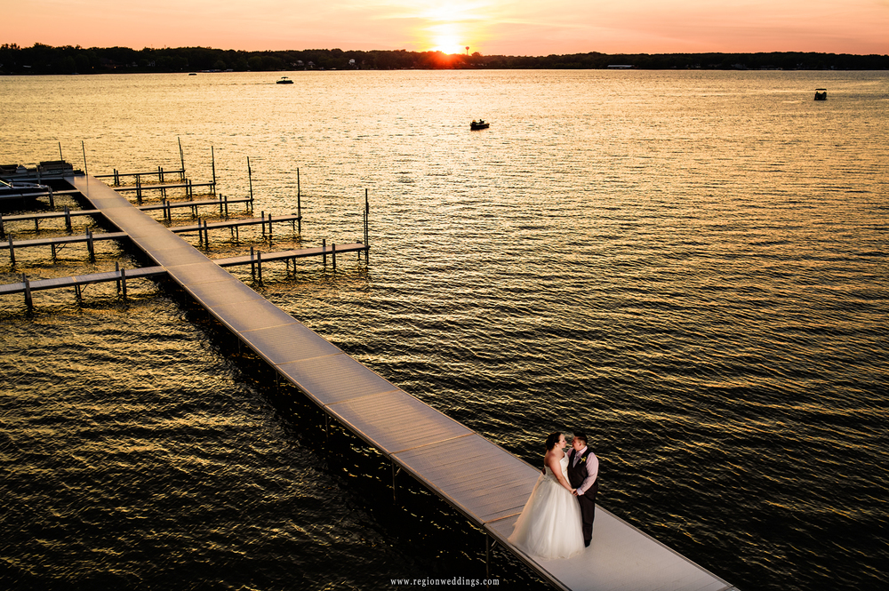 A just married couple stands alone on the pier as the sun sets off Cedar Lake.