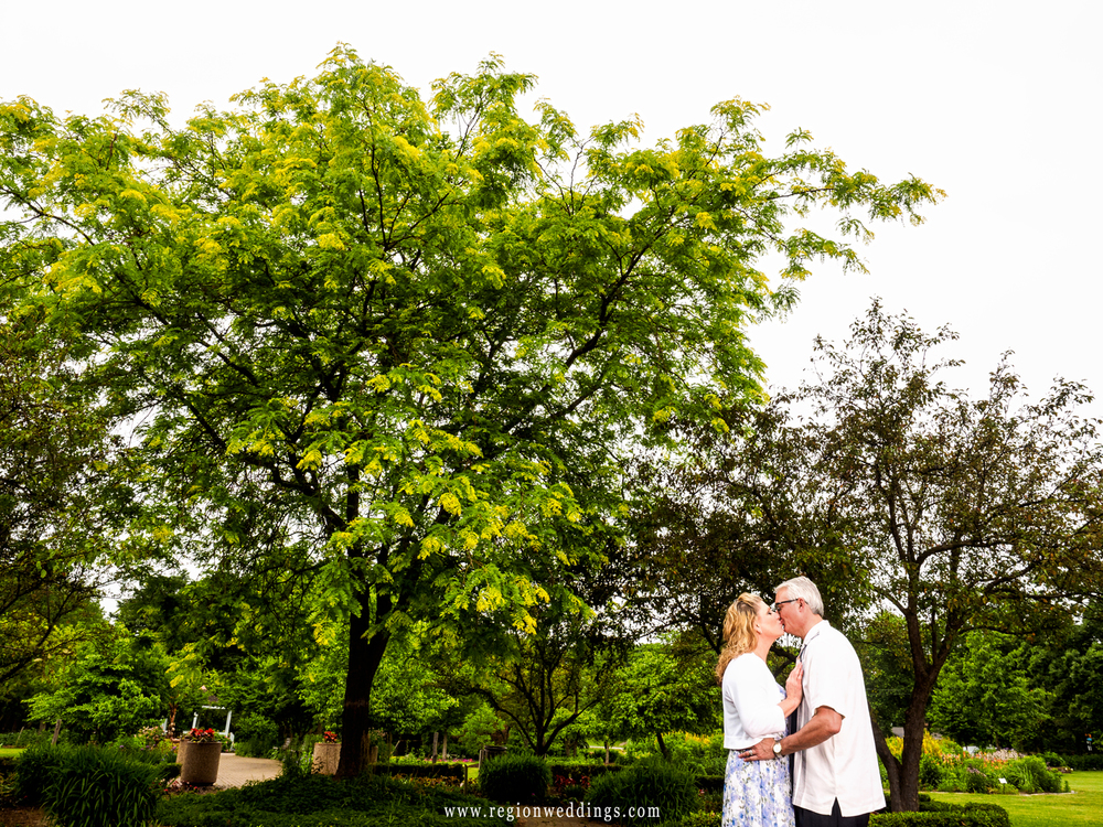 The happy couple shares a kiss beneath the trees at Ogden Gardens in Valparaiso, Indiana.