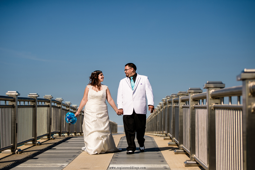 Bride and groom take a walk on the pier.