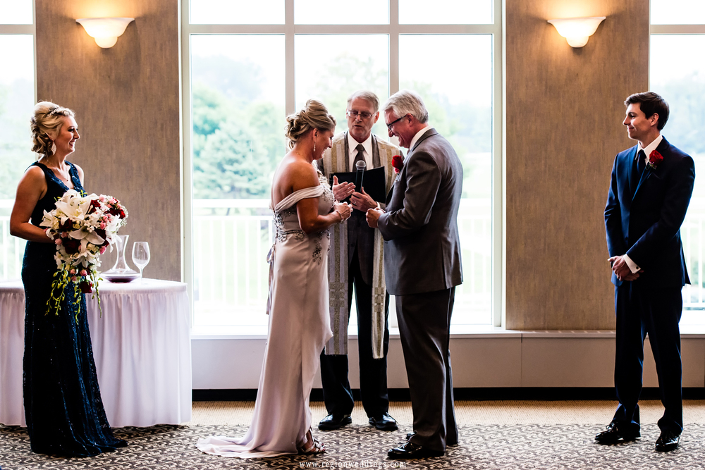Bride and groom exchange vows and rings at Sand Creek Country Club.