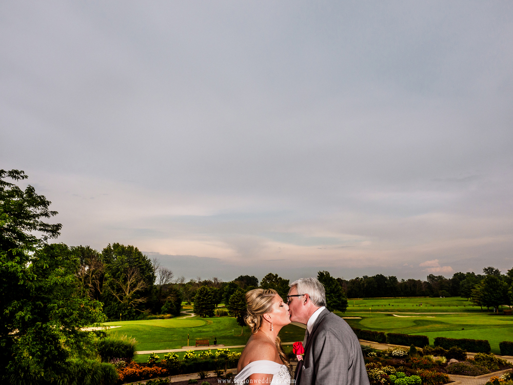 The newly married couple kisses on the balcony overlooking Sand Creek Golf Course in Chesterton, IN.