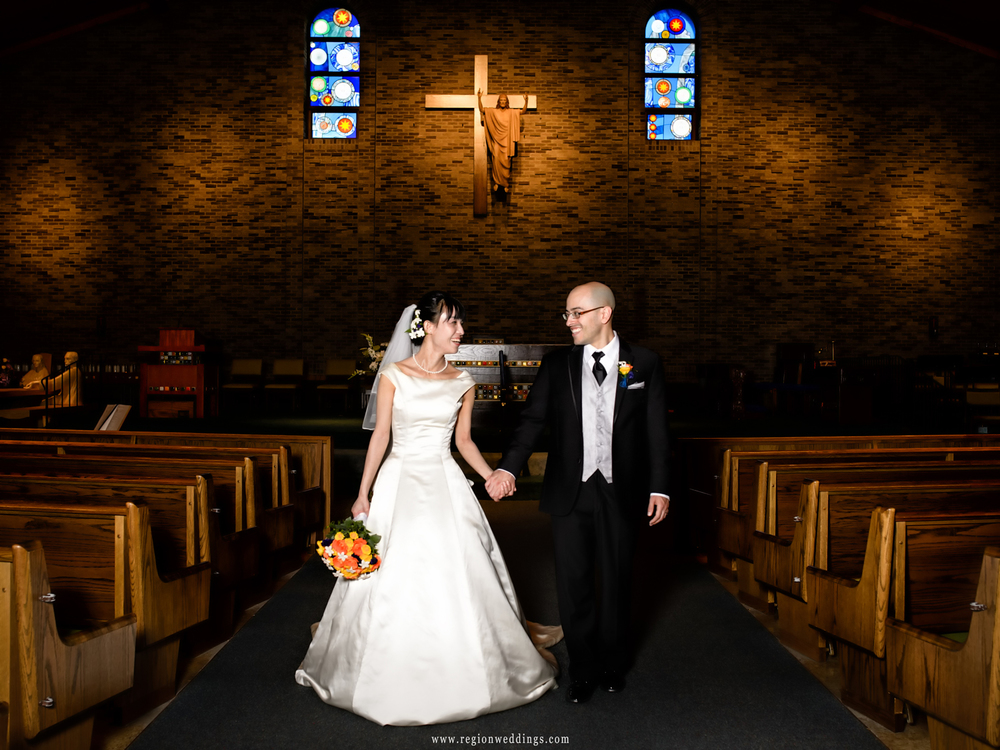 Bride and groom walk down the center aisle at St. Maria Goretti Church in Dyer, Indiana.