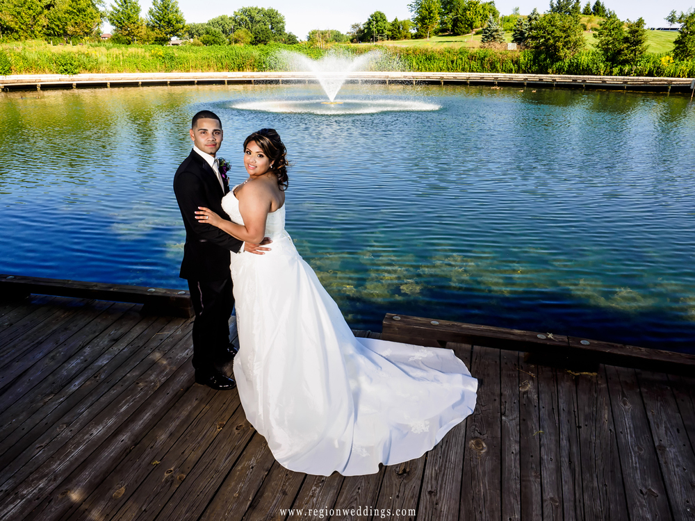 The bride and groom embrace at the fountain of Centennial Park as the blue sky reflects off the water.