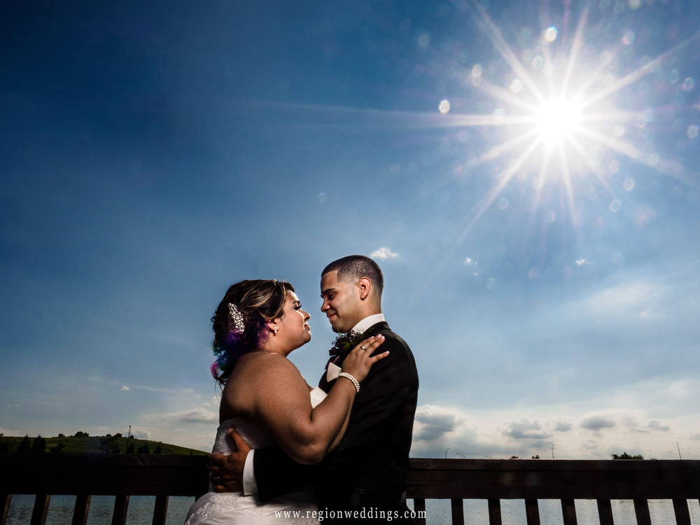 A sun star in the blue sky for this summer wedding photo of the bride and groom.