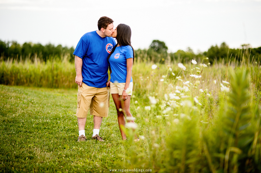 Two Chicago Cubs fans kiss in a field at Taltree Arboretum for their engagement photos.