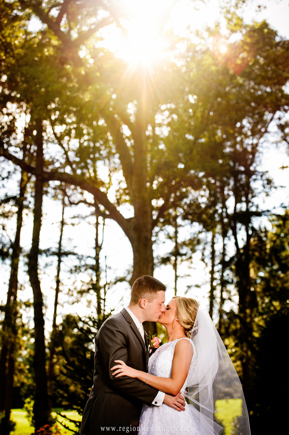 Bride and groom kiss as the sun sneaks through the trees at Sandy Pines Pavilion.