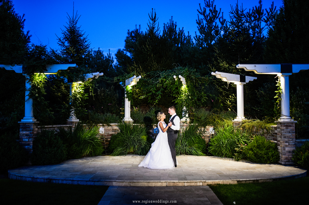 The bride and groom slow dance under the night sky at The Pavilion At Sandy Pines.