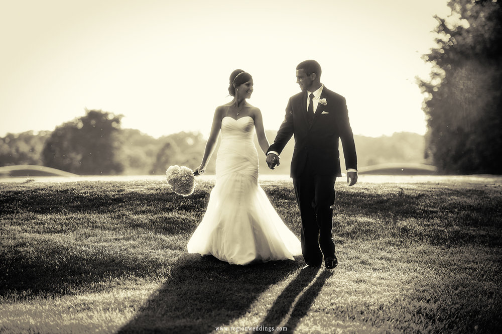 The bride and groom stroll the hills of White Hawk golf course at golden hour.