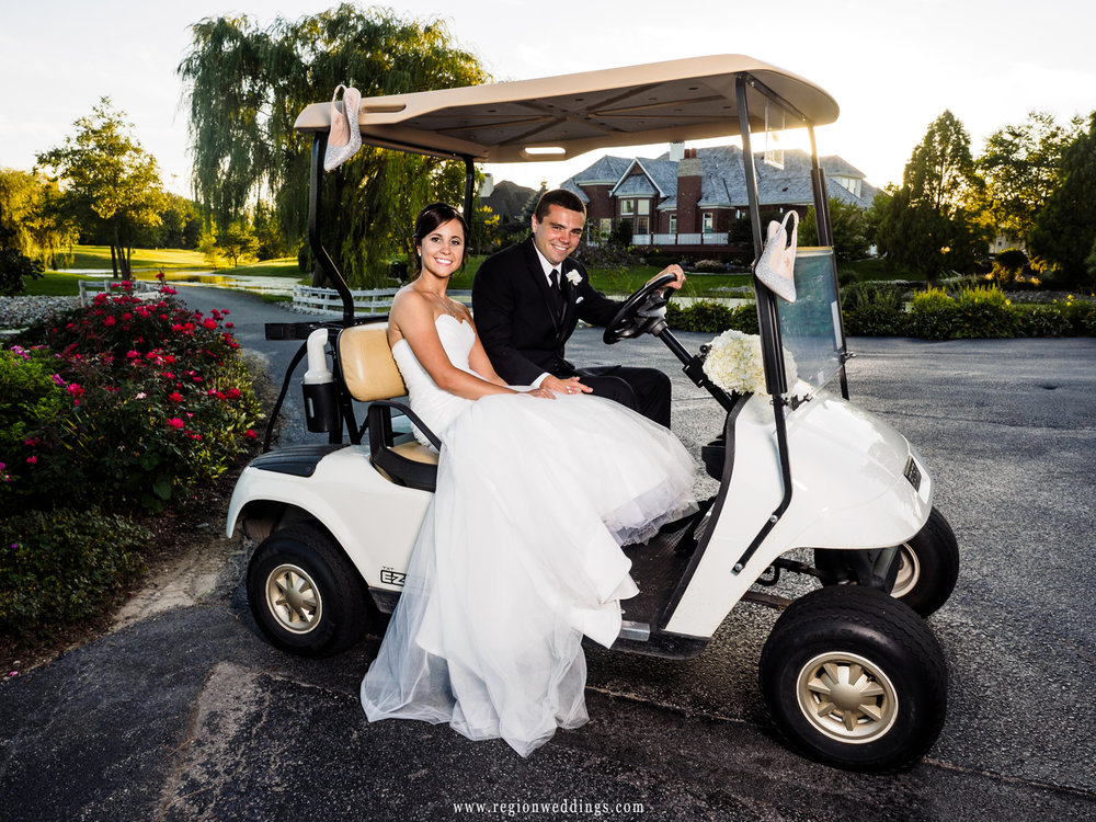 Cute wedding photo of bride and groom on a golf cart.