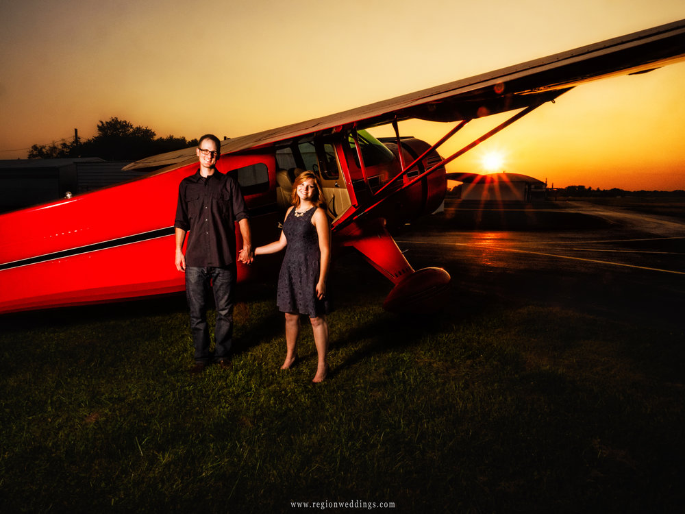 The sun sets over the airplane hangar in an aviation themed engagement portrait.