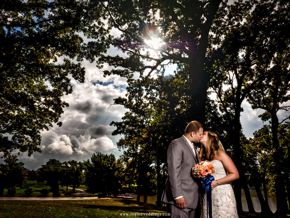 Bride and groom share a kiss hidden by trees in St. John, Indiana with sun breaking through.