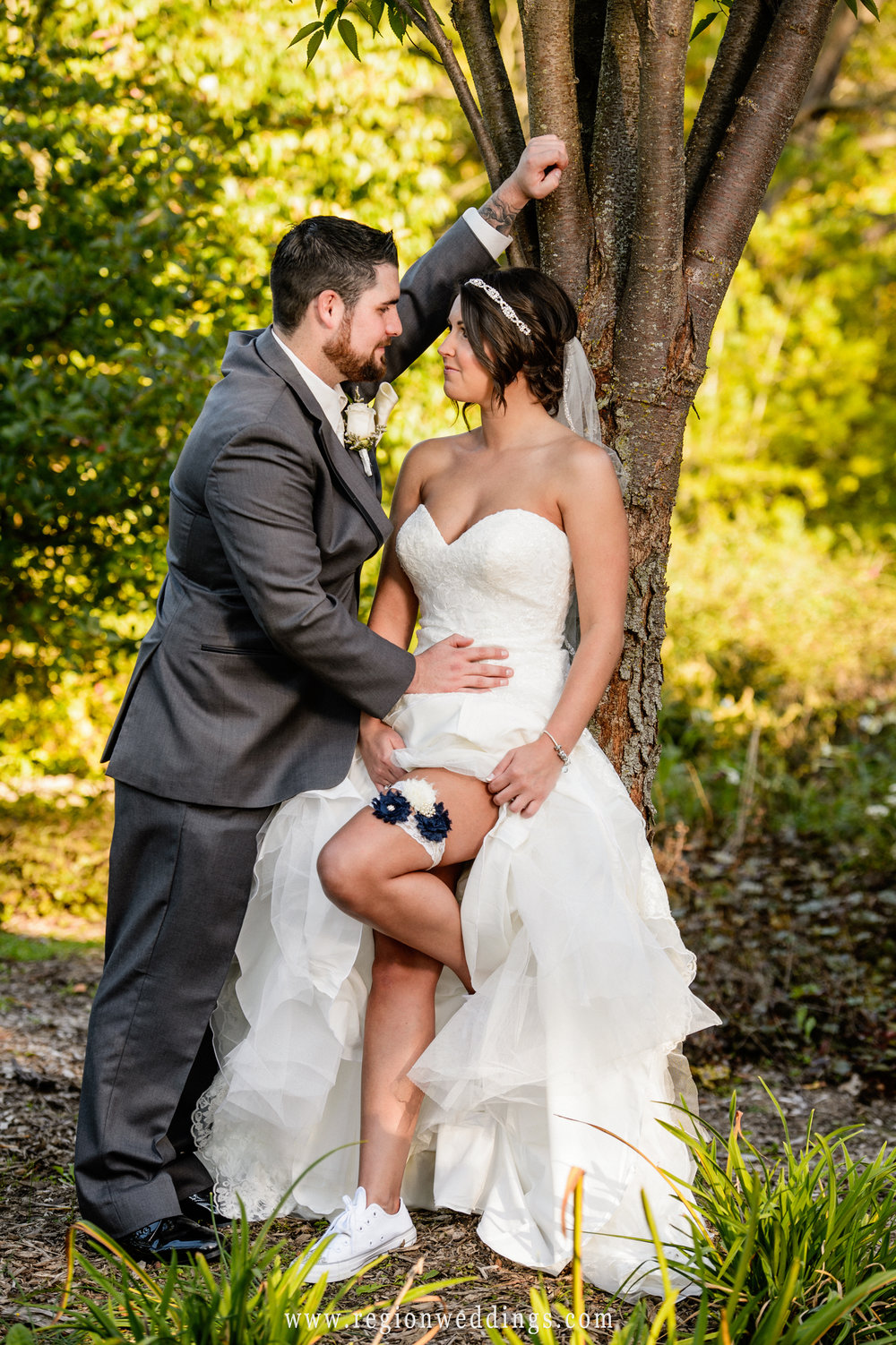 The bride shows off her garter as she shares a romantic moment with her groom.