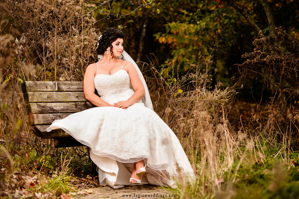 The bride rest on a bench at the edge of Ogden Gardens.