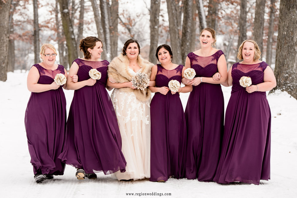 The bride and her bridesmaids take a walk in the snow filled woods of Lake County Fairgrounds.