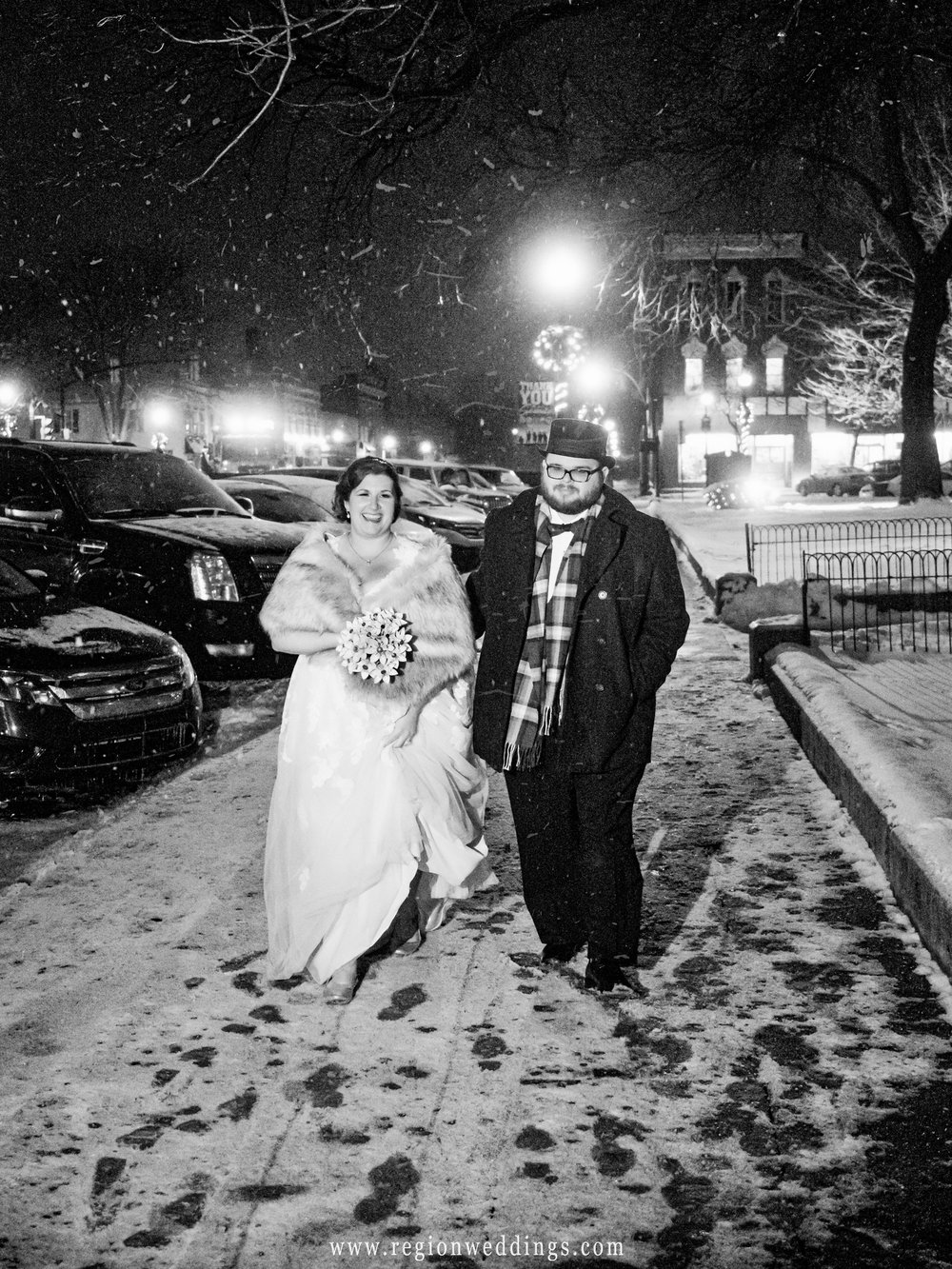 Snow fills the air as the bride and groom walk back to their limo in downtown Crown Point.