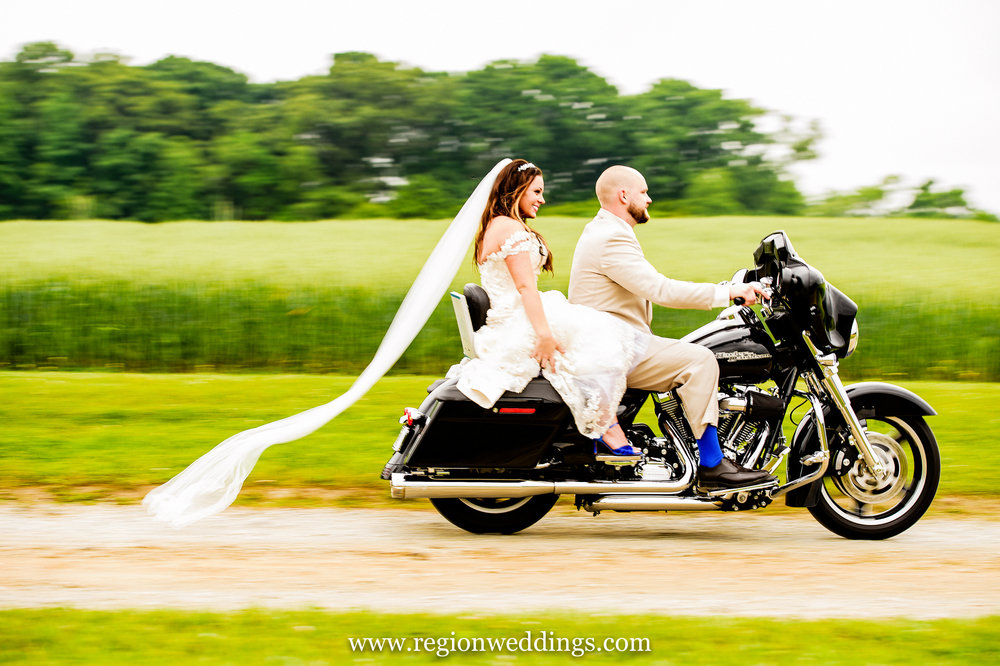 The bride and groom roar away on their Harley Davidson motorcycle.