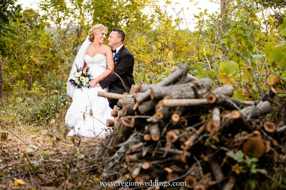 Bride and groom sit on logs at Coffee Creek Park in Chesterton, Indiana.