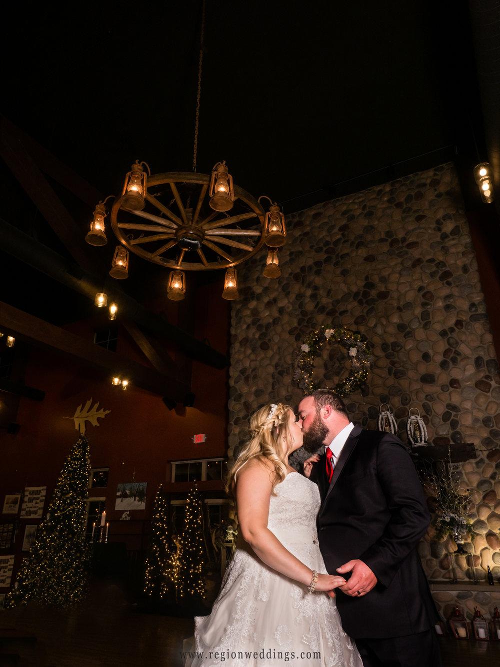 The bride and groom share a kiss in the ballroom at Fair Oaks Farmhouse.