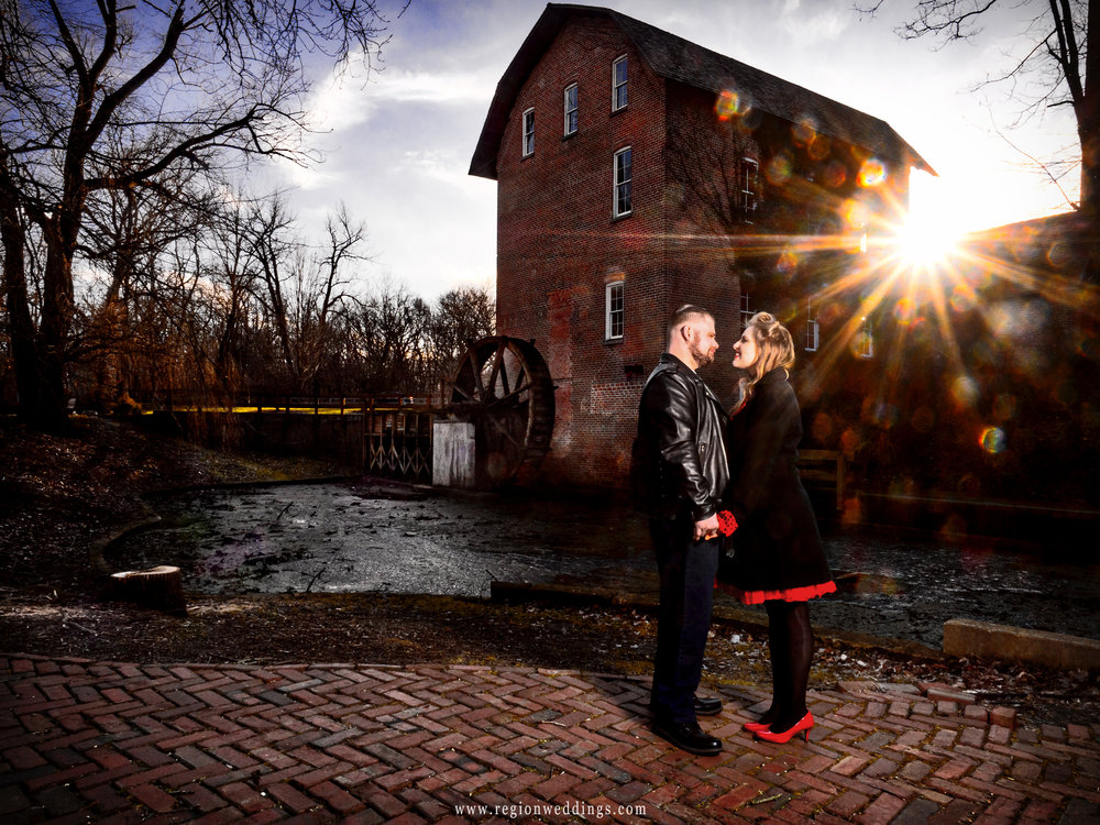 The sun bursts above the grist mill at Deep River during a winter engagement session.