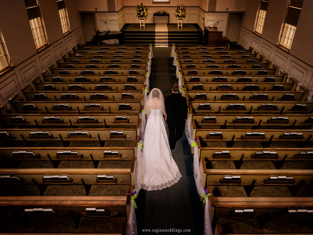 View from the balcony as the bride and groom walk the center aisle surrounded by pews and bibles.