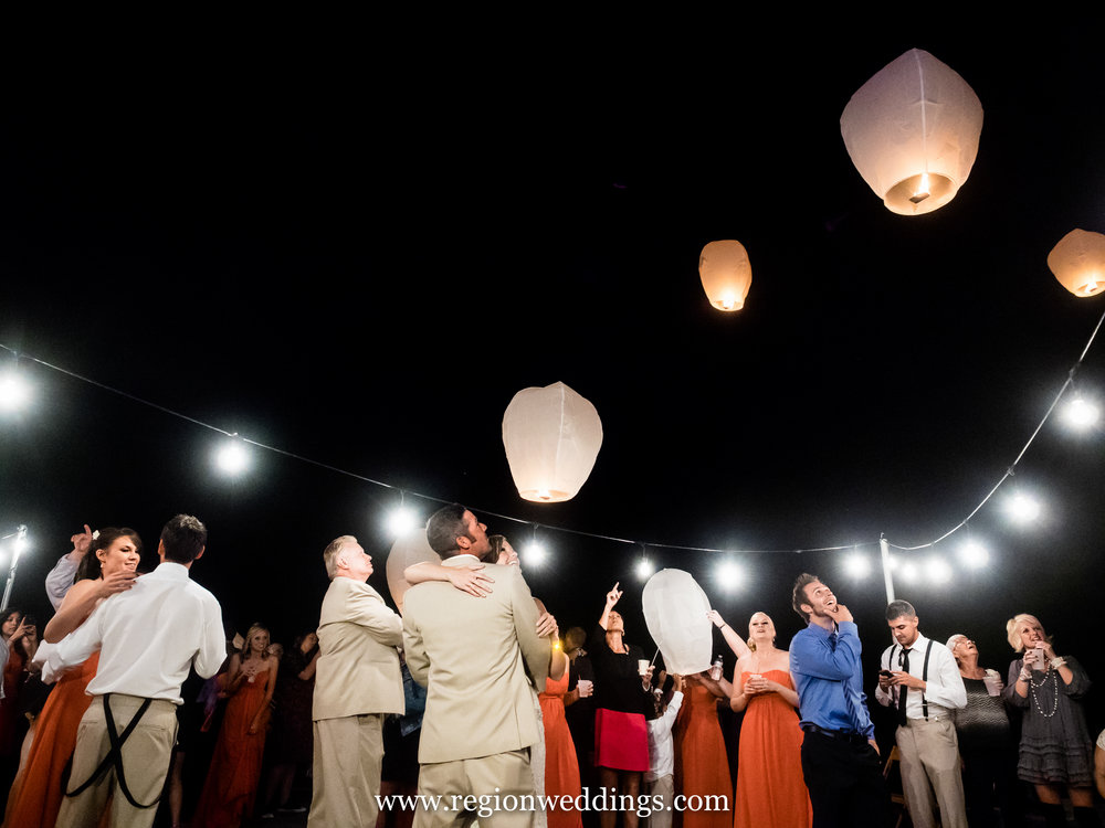 Sky lanterns fill the night sky at an outdoor wedding reception.