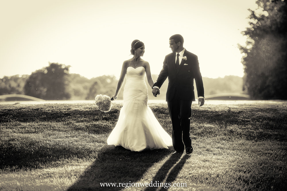Bride and groom strolling along the golf course at White Hawk Country Club.