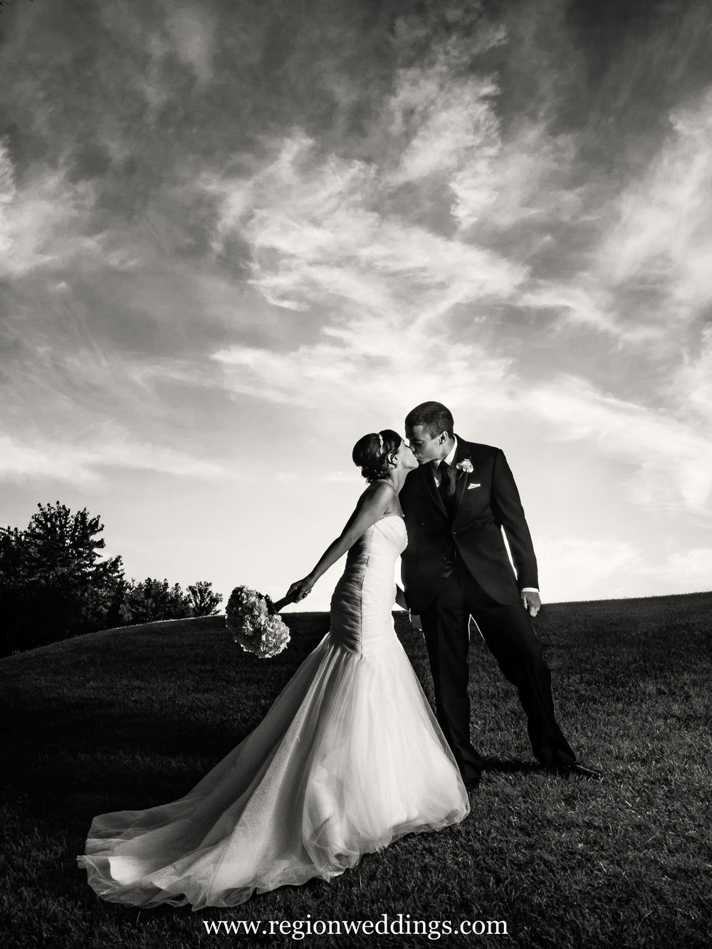 Black And White Photo Of Bride Groom Kissing On A Hill At Hawk Country
