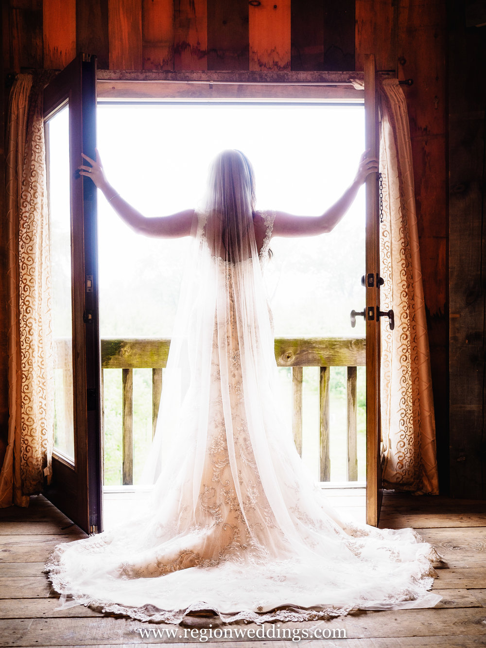 Bride opens the doors on the balcony of the bridal suite at County Line Orchard in Hobart, Indiana.