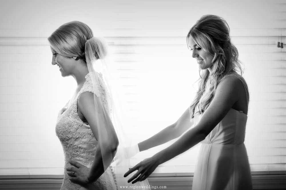 The MOH assists the bride with her veil.