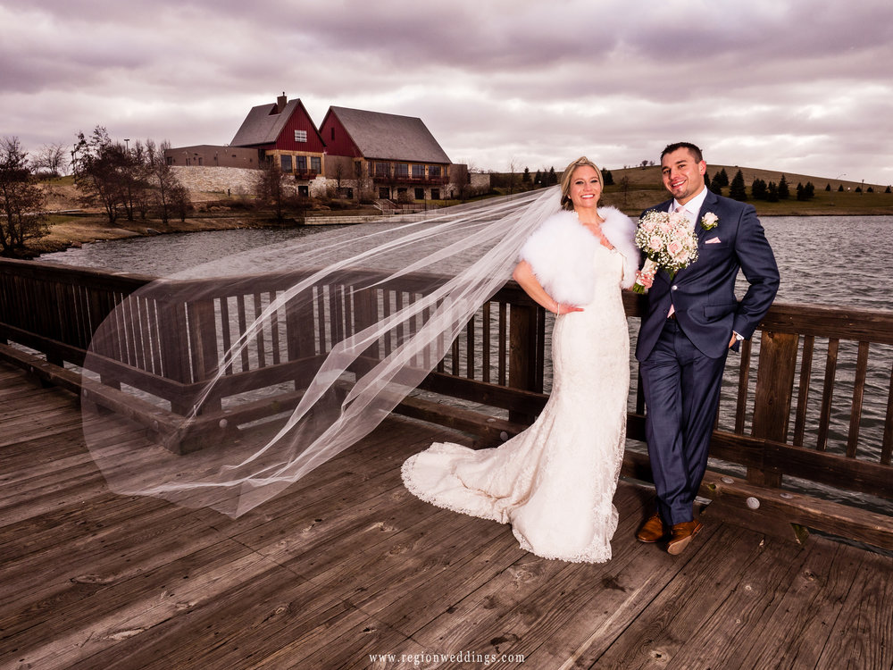 The wind carries the bride's veil on the bridge at Centennial Park.