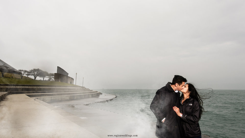 Fog engulfs a newly engaged couple on the shoreline of Lake Michigan in Chicago.