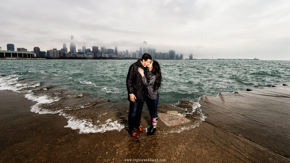 Waves from Lake Michigan crash onto the boardwalk during a Chicago engagement session.