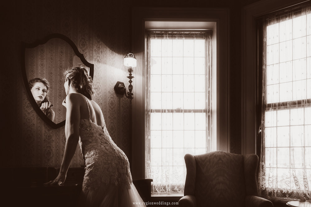 Our lovely bride applies lipstick in the bridal suite at Barker Mansion.