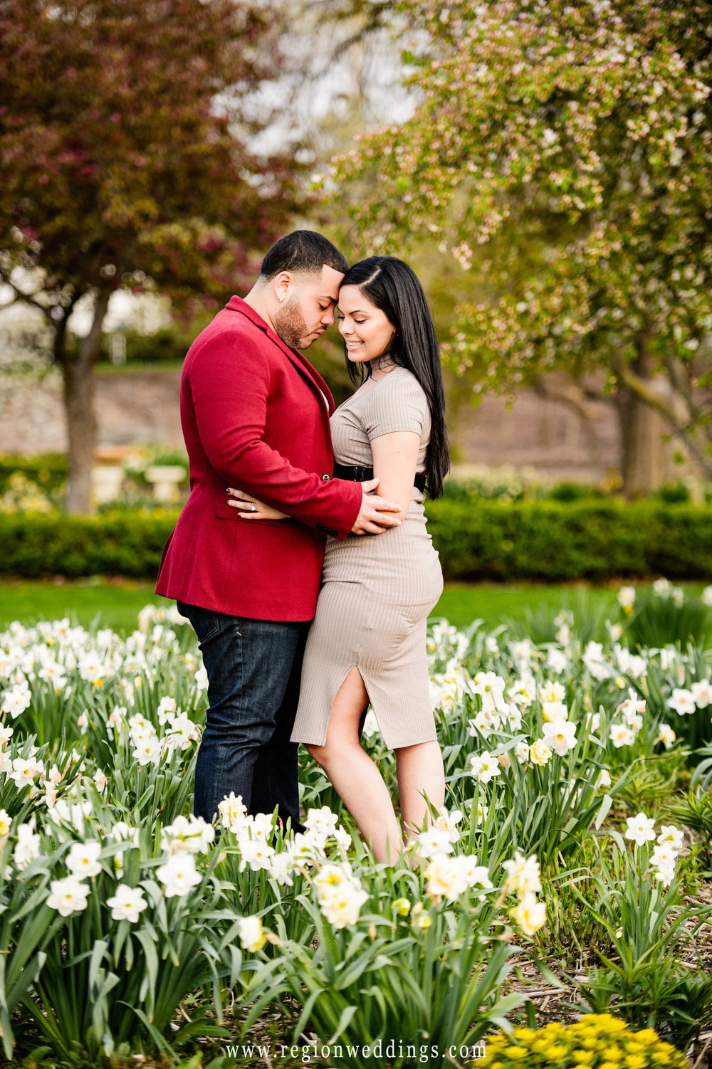 Engagement photo in a bed of flowers in Valparaiso, Indiana.