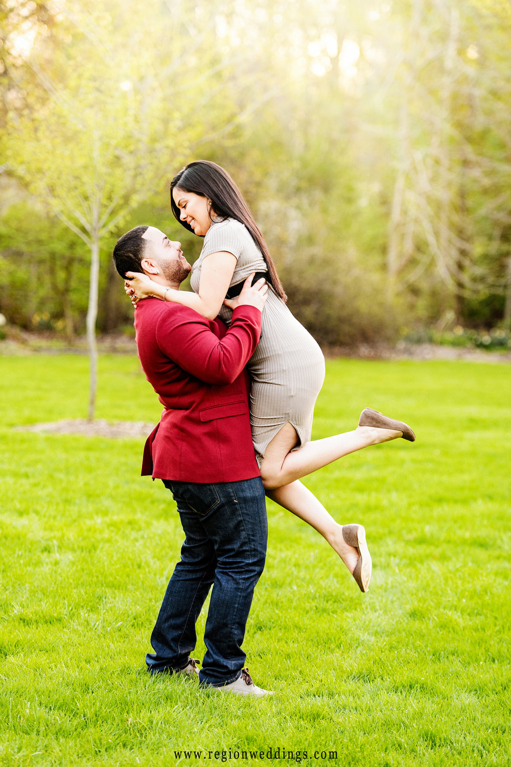 A man lifts his fiance' into the air for a romantic engagement photo.