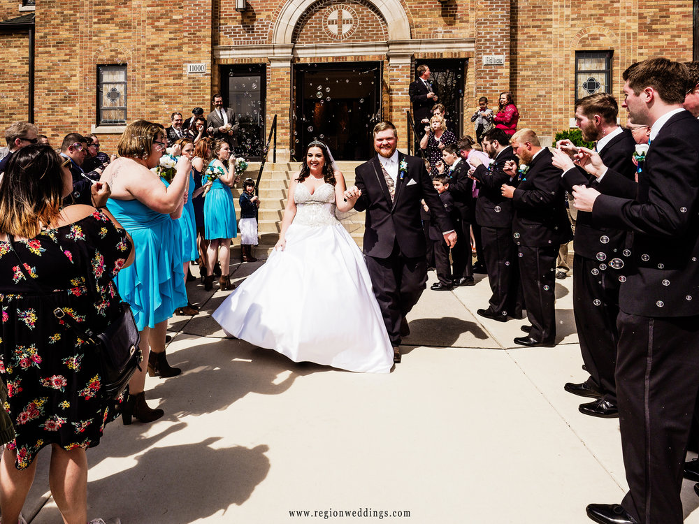 The bride and groom walk through bubbles as they exit church at their Spring wedding.