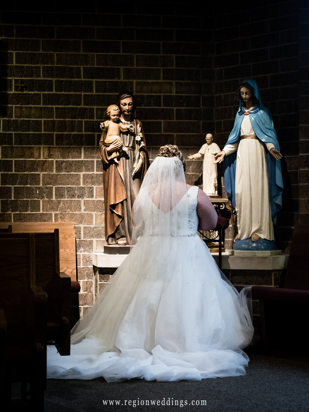 Bride kneeling in church.