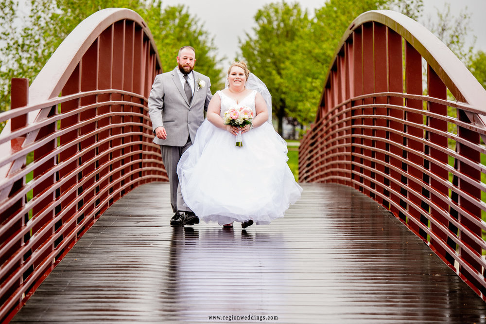 Bride and groom take a romantic walk in the rain at Centennial Park.